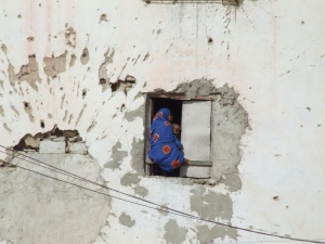 40. woman and child, on side of building to escape shelling on other side of building, Hamar Bile